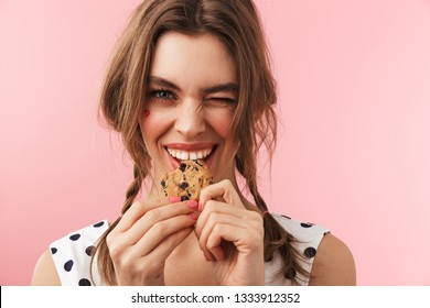 Portrait of a pretty lovely girl wearing dress standing isolated over pink background, eating chocolate chip cookie