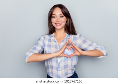 Portrait of pretty, lovely, nice woman showing heart figure with fingers over grey background