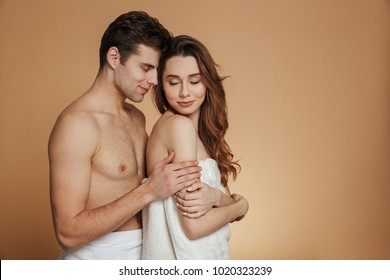 Portrait of a pretty loving shirtless couple embracing while standing isolated over beige background
