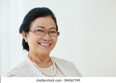 Portrait of pretty mature Vietnamese woman smiling at camera