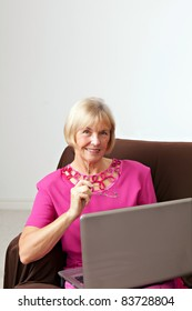 Portrait of a pretty and mature woman. She is sitting on a sofa working on a computer.