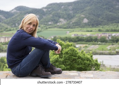 Portrait pretty mature woman sitting on a sunny day relaxed and happy on limestone wall, with a mountain background