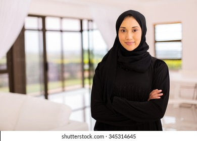portrait of pretty muslim woman with arms crossed at home