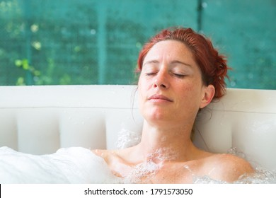 Portrait of Pretty natural redheaded woman relaxing in her bubble bath