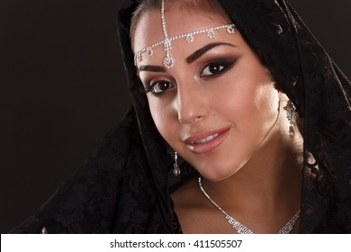 Portrait of Pretty oriental woman in abaya on black background