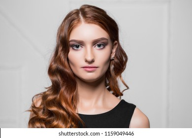 Portrait of pretty red-haired woman posing in the studio