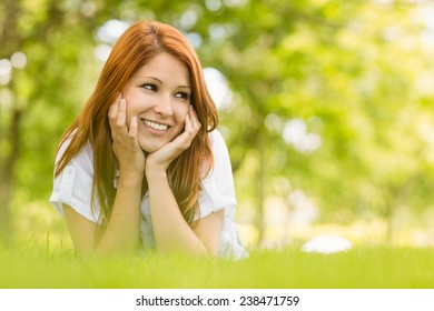 Portrait of a pretty redhead happy and lying on grass in park