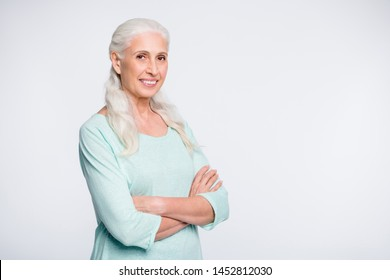 Portrait of pretty retiree with crossed arms looking at camera smiling wearing turquoise sweater isolated over white background