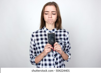 Portrait of a pretty sad woman  in plaid shirt holding smartphone with broken screen standing over gray background and looking at left side