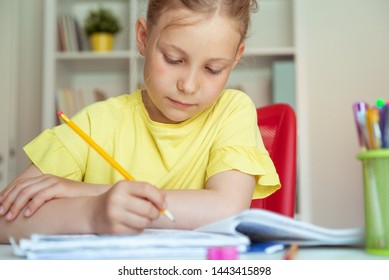 Portrait of pretty school girl in yellow are studying at classroom at the table
