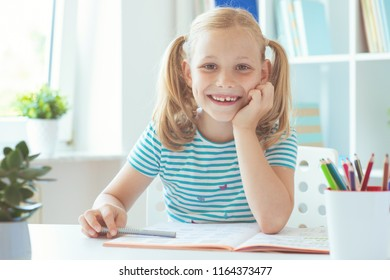 Portrait of pretty schoolgirl at classroom writing at the table