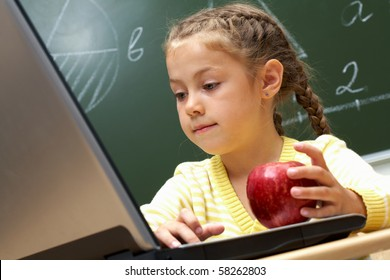 Portrait of pretty schoolgirl looking at the laptop attentively