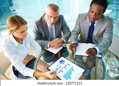 Portrait of pretty secretary pointing at paper while explaining something to her boss and colleague