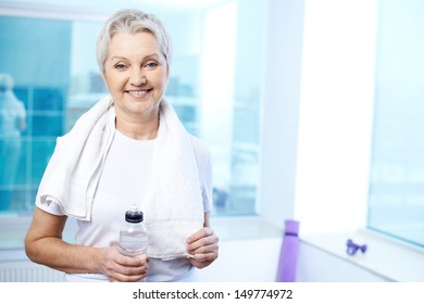 Portrait of pretty senior woman with towel and bottle of water in gym