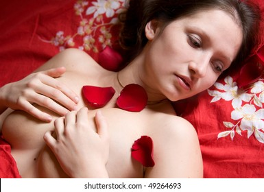 Portrait of pretty sensual young  girl with rose petals