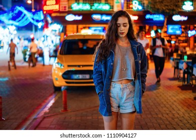 Portrait of pretty serious girl walking in the night neon lights city