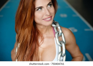portrait pretty sexy athletic young redhead Caucasian girl working out training in gym weight pumping up muscles and poses fitness and bodybuilding concept