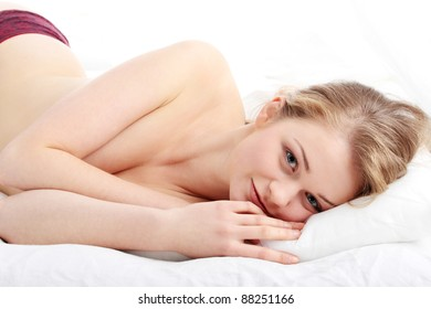 Portrait of pretty sexy blond woman on the bed.