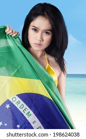 Portrait of pretty sexy woman holding brazilian flag. shoot at beach
