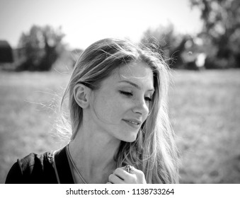 Portrait of pretty and shy young women smiling and not looking away of the camera. End of summer, autmn, countryside.