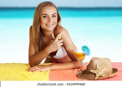 Portrait of a pretty smiling female with pleasure spending time on the beach,  uses a sunscreen spray for a safe tan, applying anti-aging moisturizing cream for staying under the sun, healthy tan