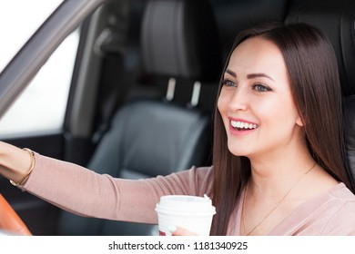 Portrait of pretty smiling friendly girl driver in a car with a paper cup
