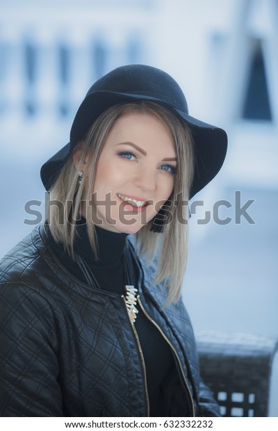 Portrait of a pretty smiling girl in black hat