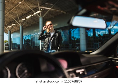 Portrait of pretty smiling girl through windshield of black cabriolet car with airport on background