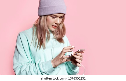 Portrait of pretty smiling lady using mobile phone to surf internet and listening to music. Female looking at smartphone screen with joy and interest. Isolated on pink