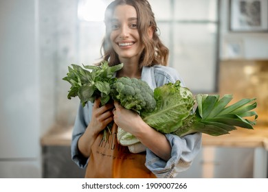 Portrait of pretty smiling woman with fresh broccoli, roman salad, basil on the kitchen with steam on background. Healthy green vegetable concept. Close up. High quality photo
