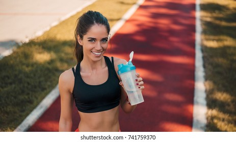 Portrait of pretty smiling woman holding bottle of watter.