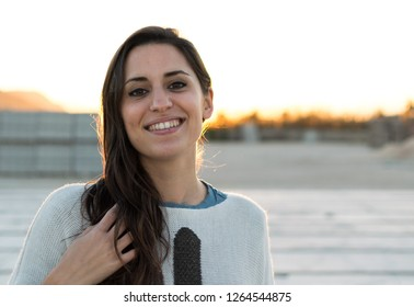 Portrait of pretty smiling woman looking at camera against sunet.