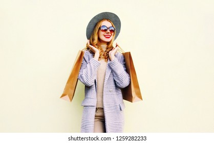 Portrait pretty smiling woman with shopping bags in pink coat, round hat on wall background