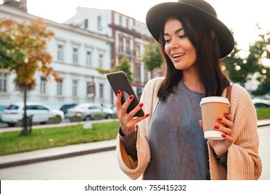 Portrait of a pretty smiling woman using mobile phone while holding coffee cup on a city street
