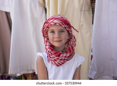 Portrait of a pretty smiling young 6 year old caucasian girl wearing a traditional Arabic headress, a keffiyeh, in a tourist shop in Sharjah in the United Arab Emirates.