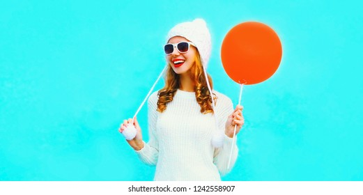 Portrait pretty smiling young woman holding in hand red air balloon in white knitted sweater, hat on blue wall background