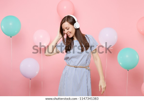 Portrait of pretty smiling young woman with closed eyes with headphones in blue dress listening music on pink background with colorful air balloons. Birthday holiday party people sincere emotions