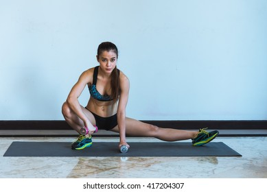Portrait of pretty sporty fitness woman working out with dumbbell