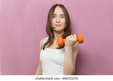 portrait of pretty sporty girl holding weights woman with dumbbells on a pink background, sports