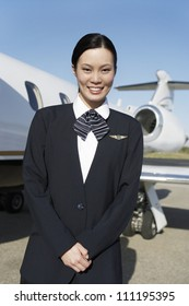 Portrait of a pretty stewardess standing on airfield