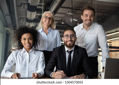 Portrait of pretty successful multi-ethnic corporate close-knit team concept, arabian european african ethnicity office workers pose look at camera four highly paid skilled specialists command indoors