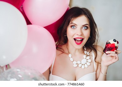 Portrait of pretty surprised brunette bride-to-be with berry cupcake and pink air balloons.