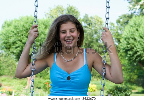 Portrait of a pretty teenage girl outside sitting on a swing.
