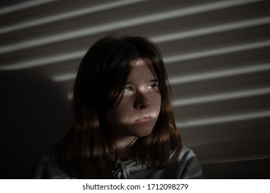 portrait of a pretty teenage girl with a shadow on her face from the blinds