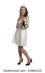 Portrait of pretty teenage girl wearing a crown and holding bouquet of flowers against white background