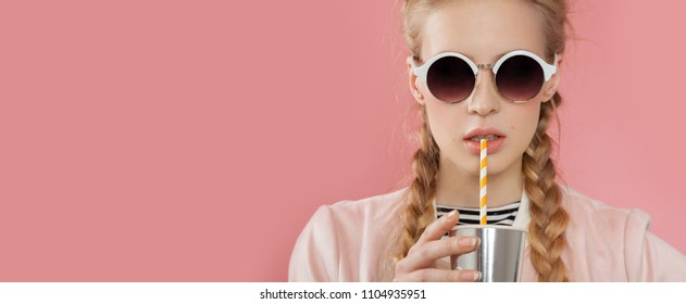 Portrait of pretty teenager in glasses drinking cocktail with straw. Joyous blonde in stylish clothes with beautiful pigtails. Isolated on pink background