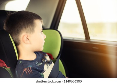 Portrait of pretty toddler boy sitting in car seat looking at window. Child transportation safety