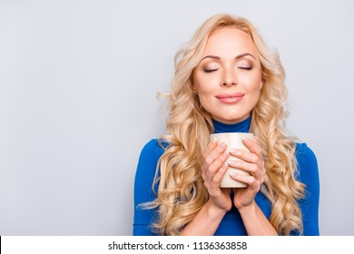Portrait of pretty, trendy, charming, nice, sexy, cute woman with close eyes in blue roll neck isolated on grey background holding mug with tea in hands enjoying smell of coffee, having pleasure