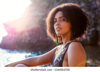 portrait of a pretty Venezuelan woman relaxing on a rock in the sea