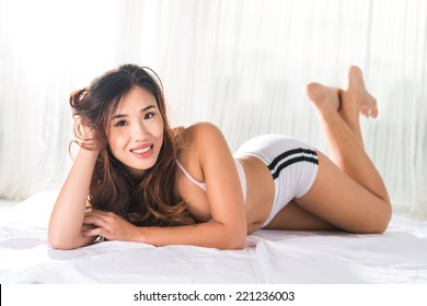 Portrait of pretty Vietnamese woman lying on the bed and looking at the camera